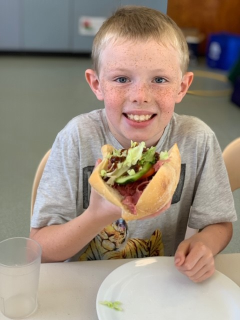 child eating a healthy salad roll