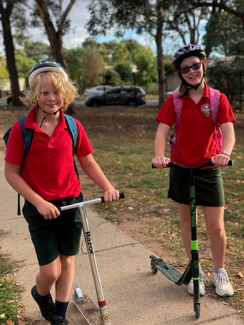 a photo of children riding their scooters