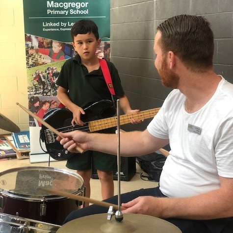 a photo of a child and his music teacher