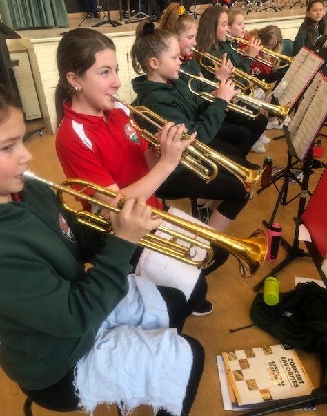 children playing brass instruments in the school band program