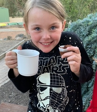 A girl drinking hot chocolate at school campat school camp
