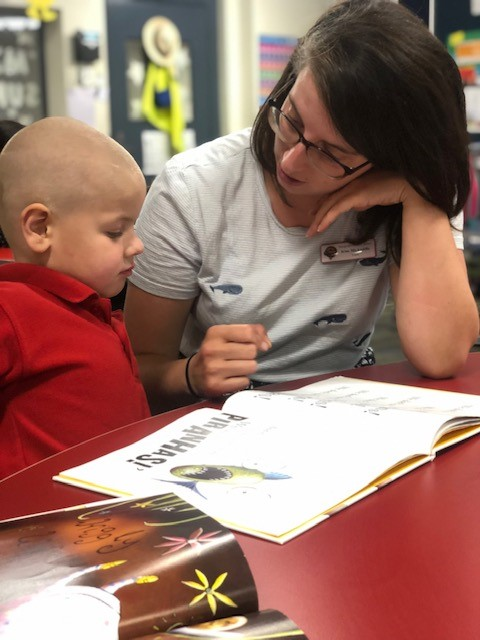 a child reading with adult support