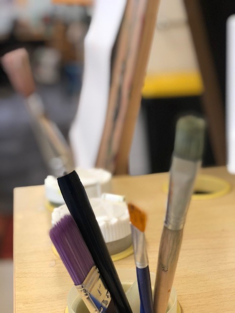 a photo of paintbrushes in a classroom