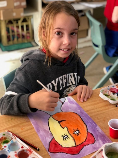 a photo of a child painting during an art class