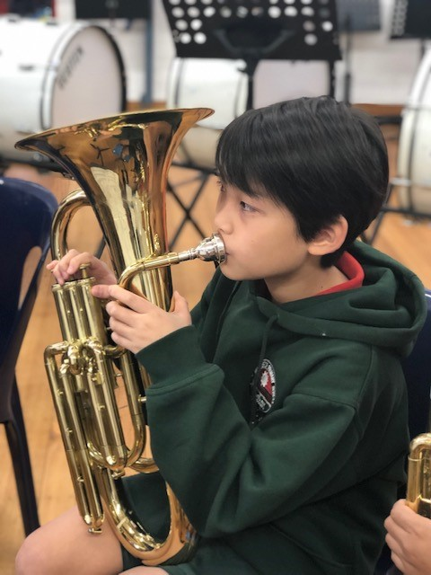 a photo of a child playing a euphonium in the school band